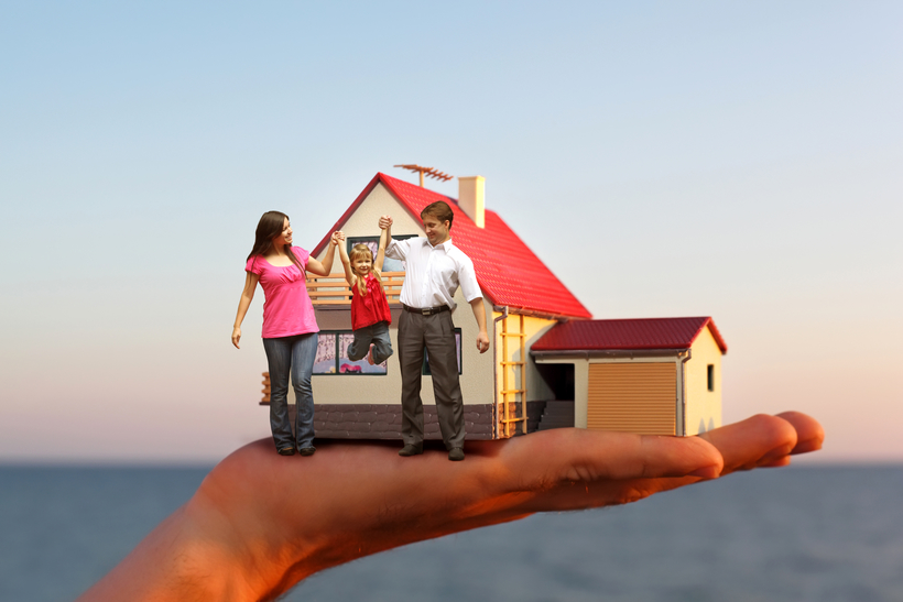 model of house with garage on hand against sea and family with g